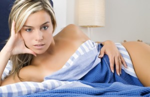 a sexy and cute blond girl between blue sheet in a bedroom